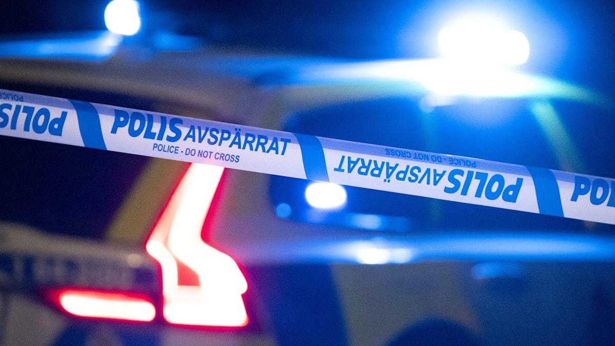 En polisbil står bakom polisavspärrningar.