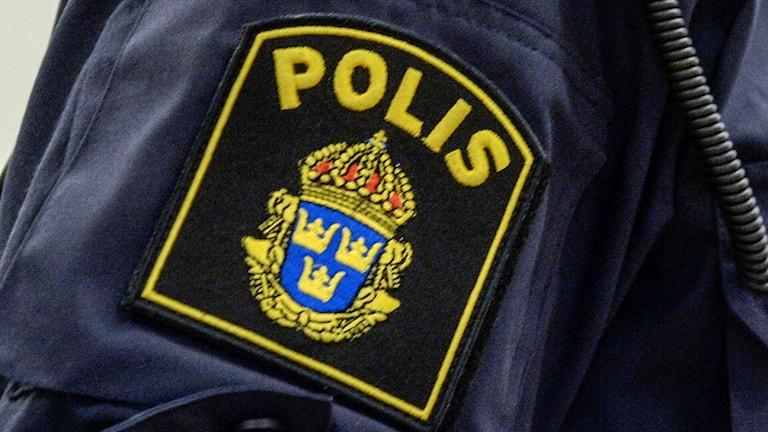 Närbild på en polisjacka med polisens emblem.
