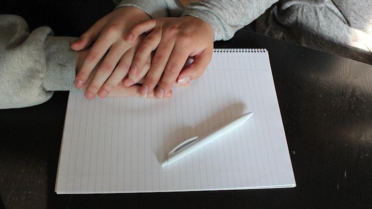 Vuxen hand på barnhänder på ett pappersblock med ett penna