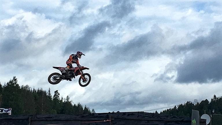 Motocross flyger över ett hopp