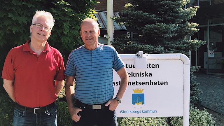 """Porträtt av Mats Olsson och Gunnar Lundberg. De står bredvid varandra med händerna i sidorna framför en skylt av """"Tekniska gatuenheten"""" på vänersborgs kommun. Solen skiner, träden är gröna och de ler mot kameran."""
