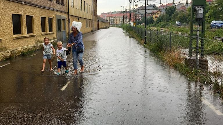 Man ser en kvinna och två barn gå i ösregnet. vägen är översvämmad och de går barfota med vatten upp till fotknölarna. Kvinnan har en plastpåse på huvudet.