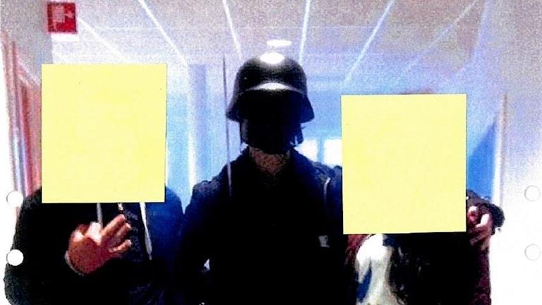 Maskerad gärningsman tar en gruppbild med två tjejer vars ansikten har täckts över med post-it av polisen.