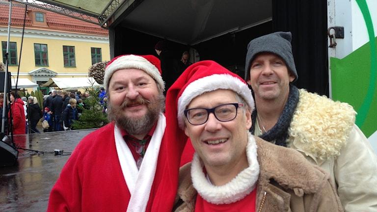 Tre ur tomteordern som uppträdde på julmarknaden. De står framför scenen.