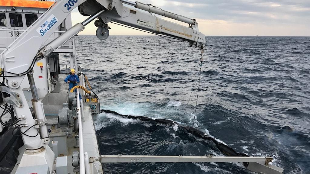 Ett av Kustbevakningens fartyg tar upp delar av oljan.