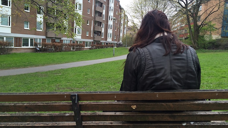 Pia på en bänk, med ansiktet bortvänt