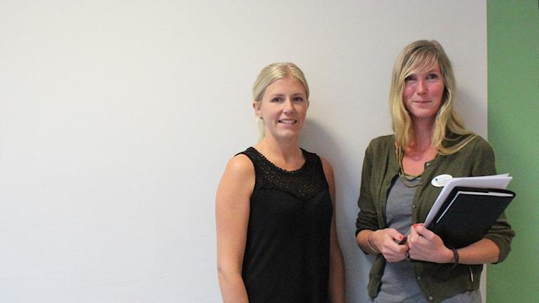 Lena Berglund och Carin Lindberg står mot en vit vägg och ser glada ut.