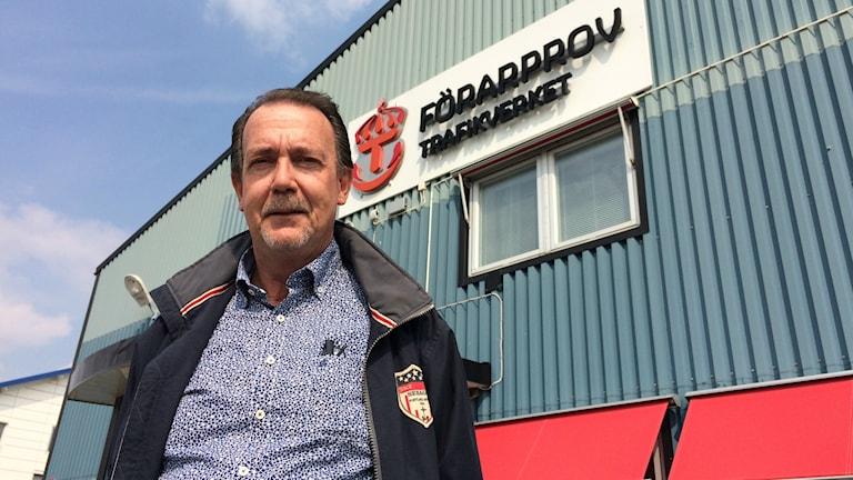 Christer Simonsson, kontorschef Trafikverket förarprov i Vänersborg, sedd snett nedifrån med Trafikverkets skylt på fasaden bakom sig.