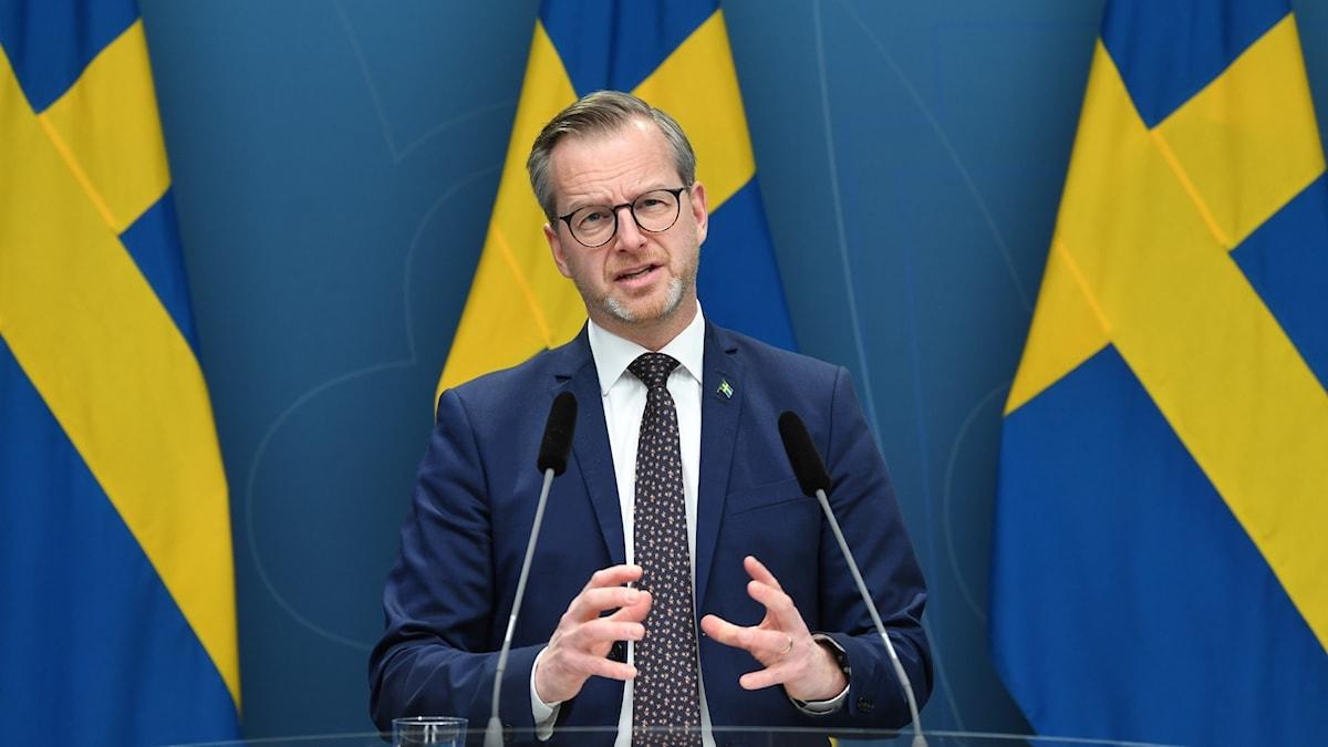 Mikael Damberg på presskonferens 24 januari. han har svenska flaggor bakom sig.