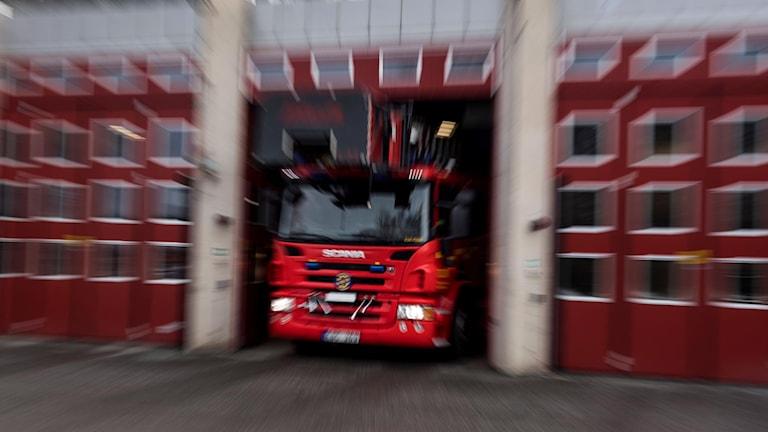 En brandbilo på väg ut från brandstationen