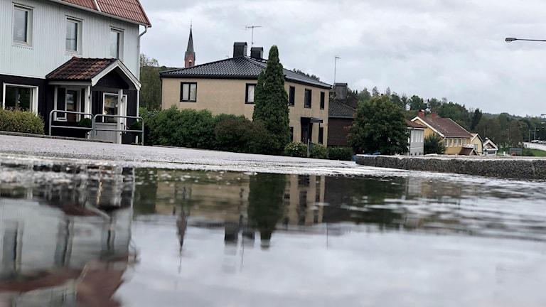 Högsäter, i Färgelanda kommun. Den nygotiska kyrkan med sin tegelfasad speglar sig i en vattenpöl längs länsväg 172. Det är en dyster och grå dag i det lilla jordbrukssamhället.