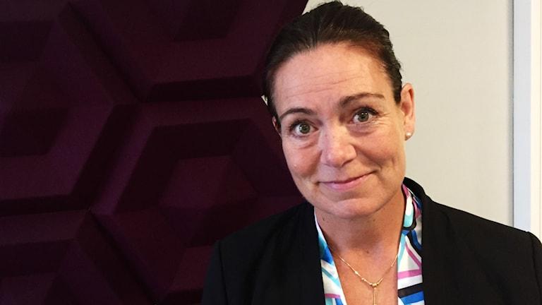 Ann-Sofie Alm (M). Oppositionsråd Munkedal. Vit kvinna. Svart hår. Snäll. Bär guldkedja.