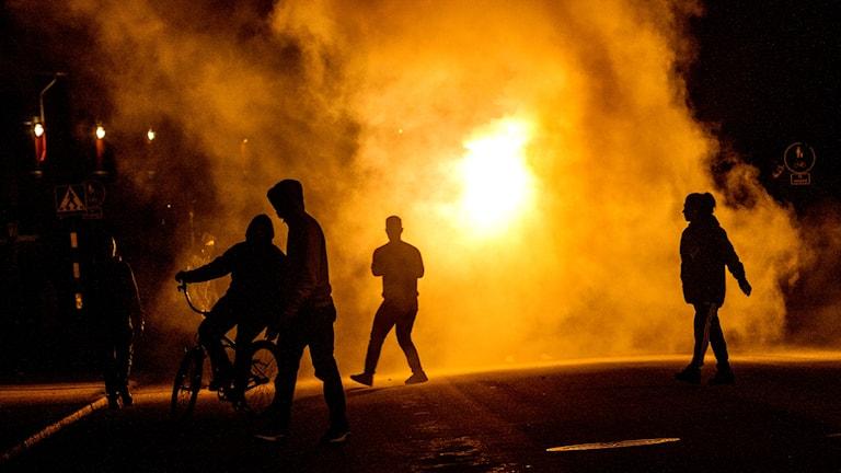 Silhuetter av ungdomar framför en eld på gatan. Foto: Joachim Nywall