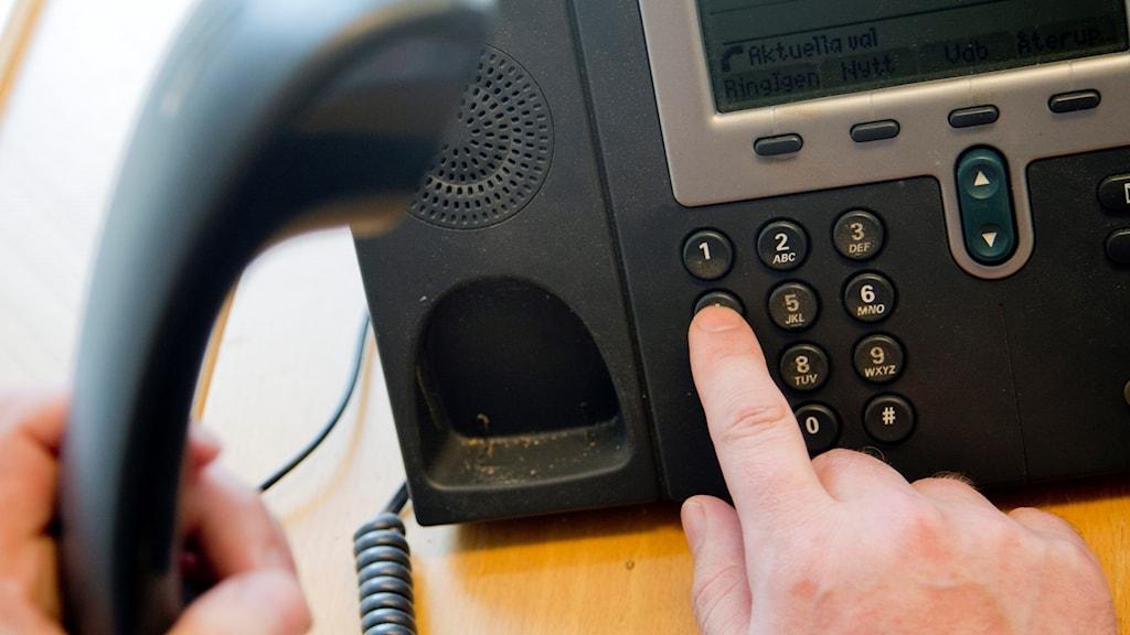 En person trycker på knapparna på en telefon.