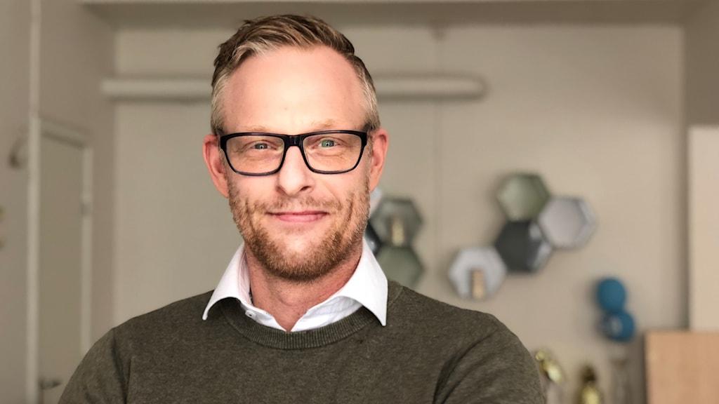 Peter Eriksson, ser glad ut, bär glasögon och står i moderaternas politikerkvarter i Trollhättan. Rummet är inrett modernt, med pastellfärger; blått, grått och grönt. Peter har på sig en militärgrön fliströja, vit skjorta, och lite skäggstubb.