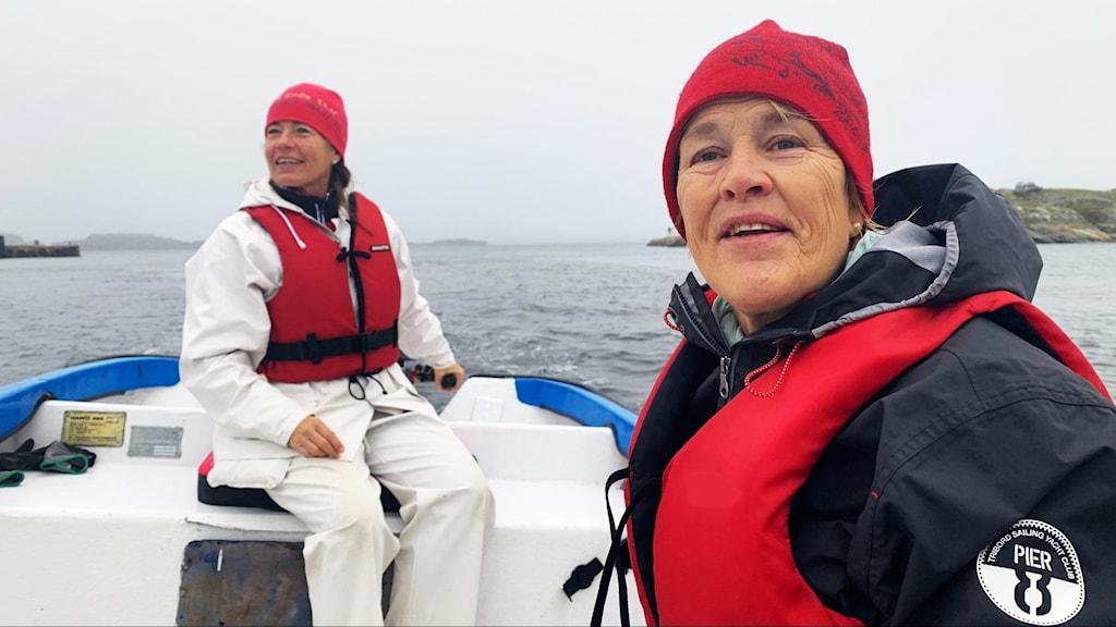 Två kvinnor i flytväst sitter i en båt till havs.