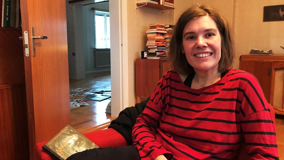 En kvinna sitter ned i bild i förgrunden, hon ler. I bakgrunden ser man högar med böcker.