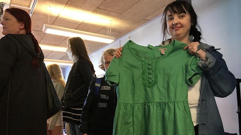 kvinna håller upp grön klänning
