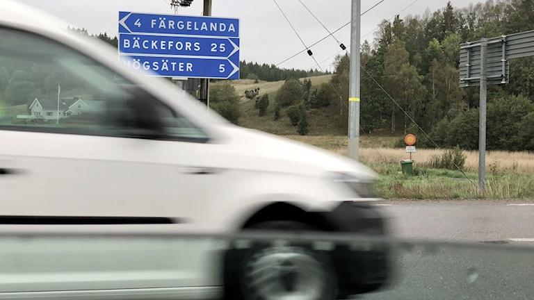 Blåa trafikskyltar, textade: Färgelanda, Bäckefors och Högsäter, med pilar åt olika håll.