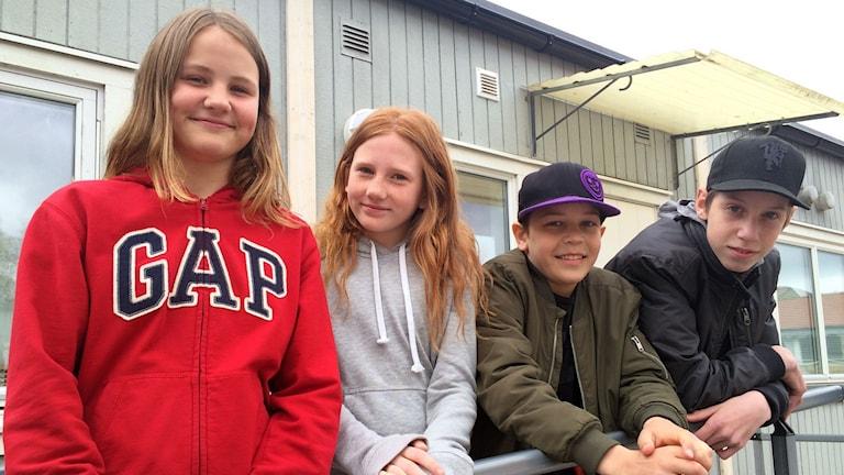 Fyra barn står bakom ett räcke. De skrattar.