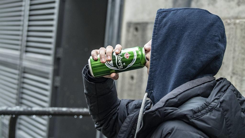en ung kille i hoodie dricker ur en ölburk.