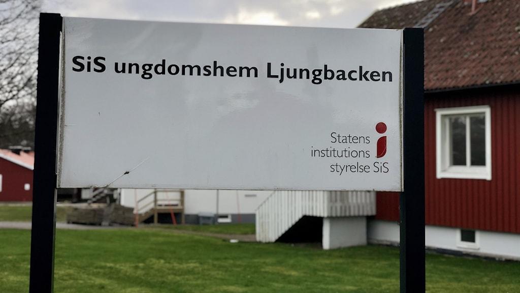 """""""SiS ungdomshem Ljungbacken"""": står det på en stor, vit skylt, som pryder ett grönområde med röda trähus."""
