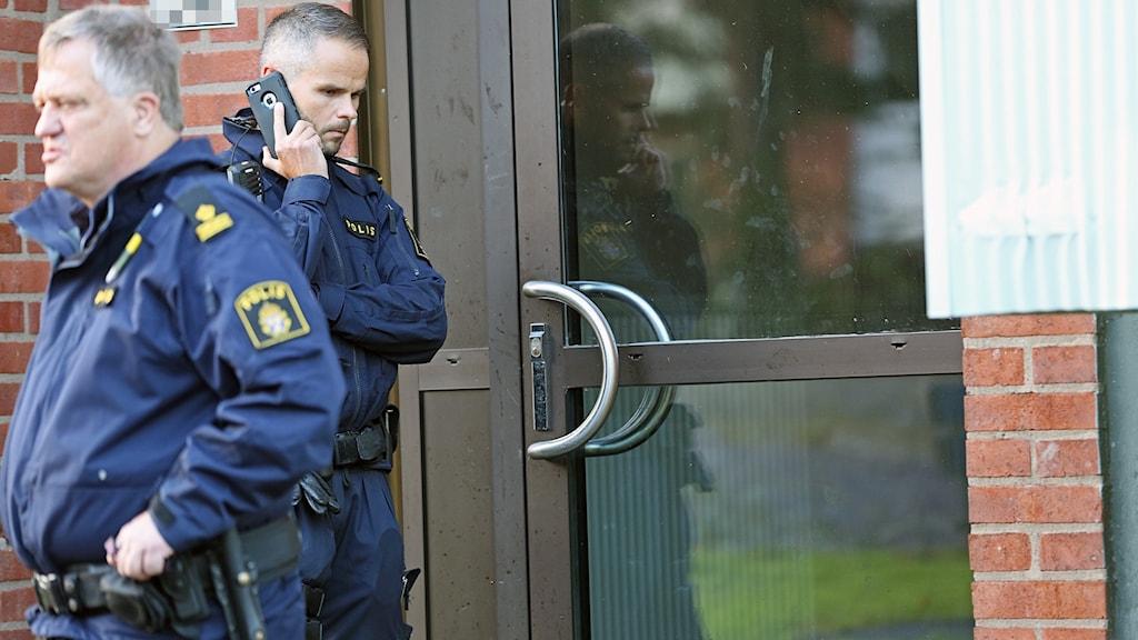 Två poliser står utanför en trappuppgångsdörr