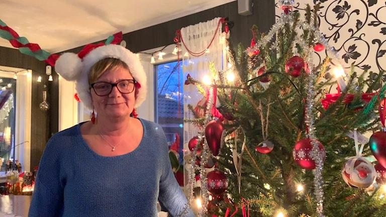 Carina Meijer framför pyntad julgran
