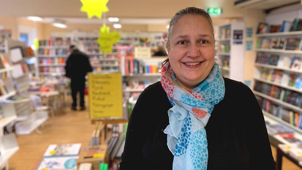 En kvinna med sjal runt halsen står i förgrunden och ler in i kameran. I bakgrunden hyllor och bord fyllda med böcker.