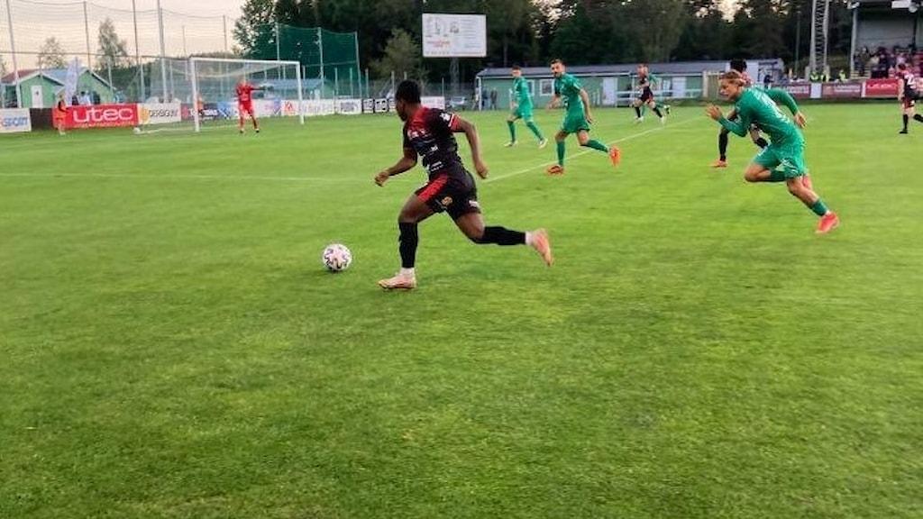Fotbollsspelare springer med bollen och jagas av motståndare