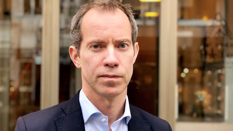 Chefsåklagare Daniel Edsbagge står framför entrén till åklagarkammaren på Kungsgatan i Uddevalla. Han bär en ljusblå skjorta till mörkblå kavaj. Han är en medelålders man med ett allvar i ögonen.