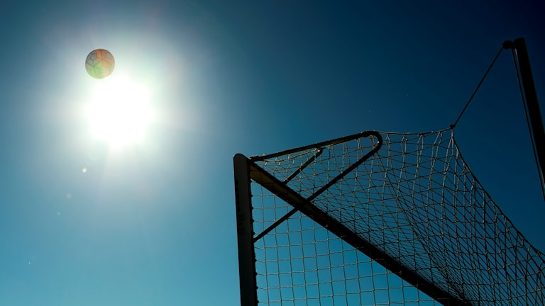 Bild på en fotboll i motljus som är på väg mot ett fotbollsmål