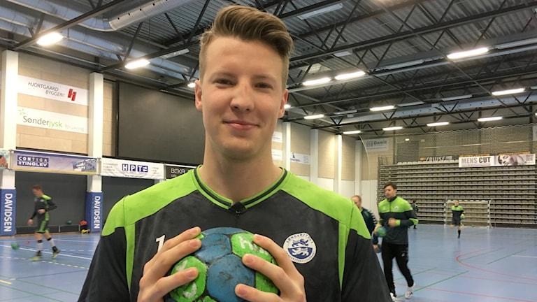 Adam Nyfjäll håller i en handboll och ler.