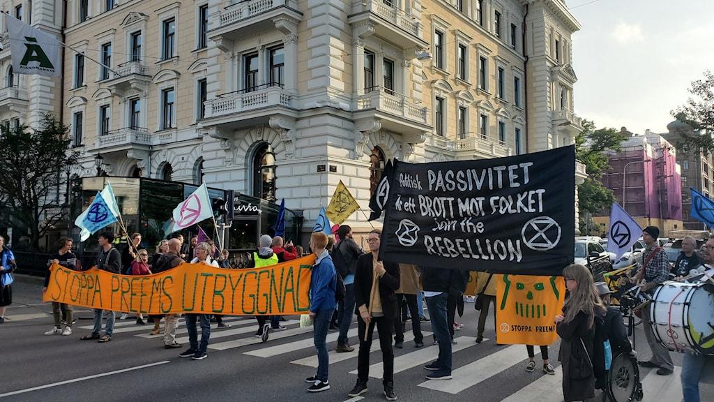 Människor med skyltar och banderoller protesterar vid ett övergångsställe.