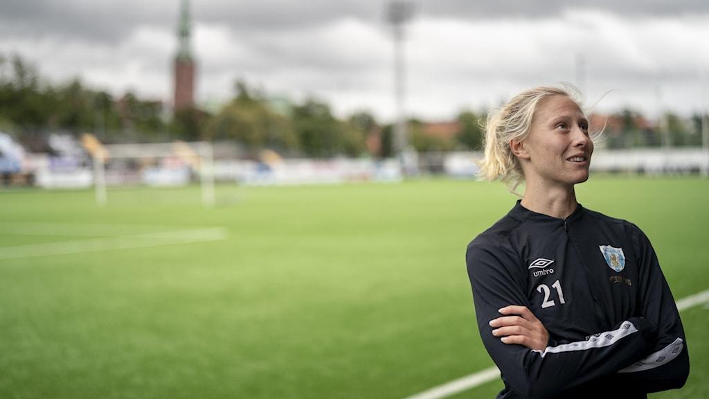 I förgunden Rebecka Blomqvist, i bakgrunden en fotbollsplan.