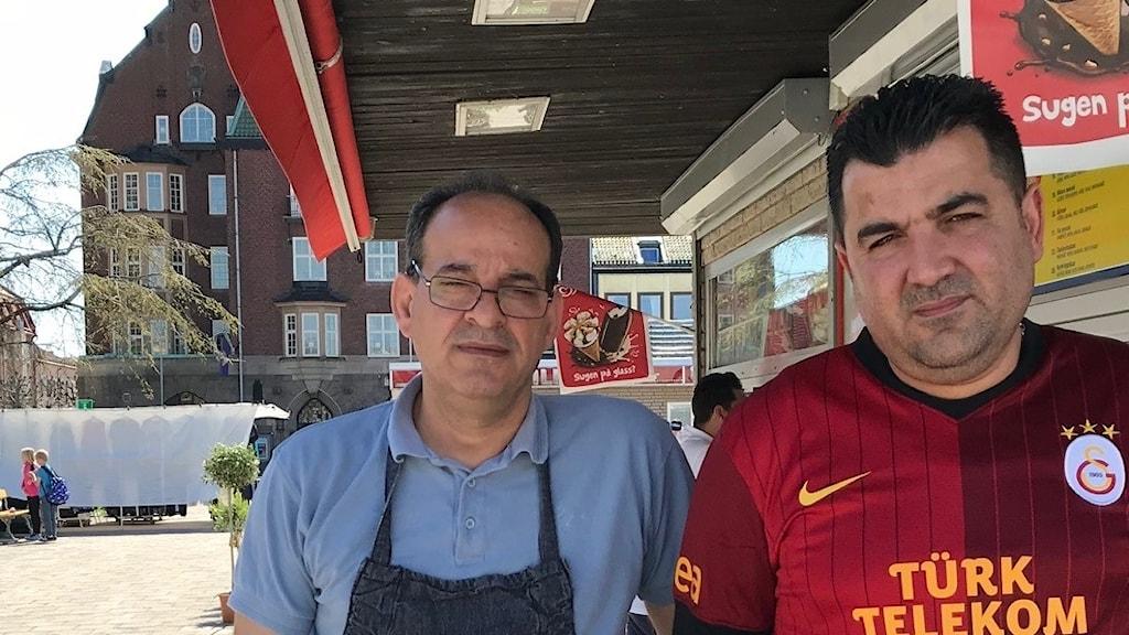 Porträtt av de två gatuköksägarna, Yousif Salih och Gökhan Korkmaz. De står på ett soligt torg i Vänersborg.