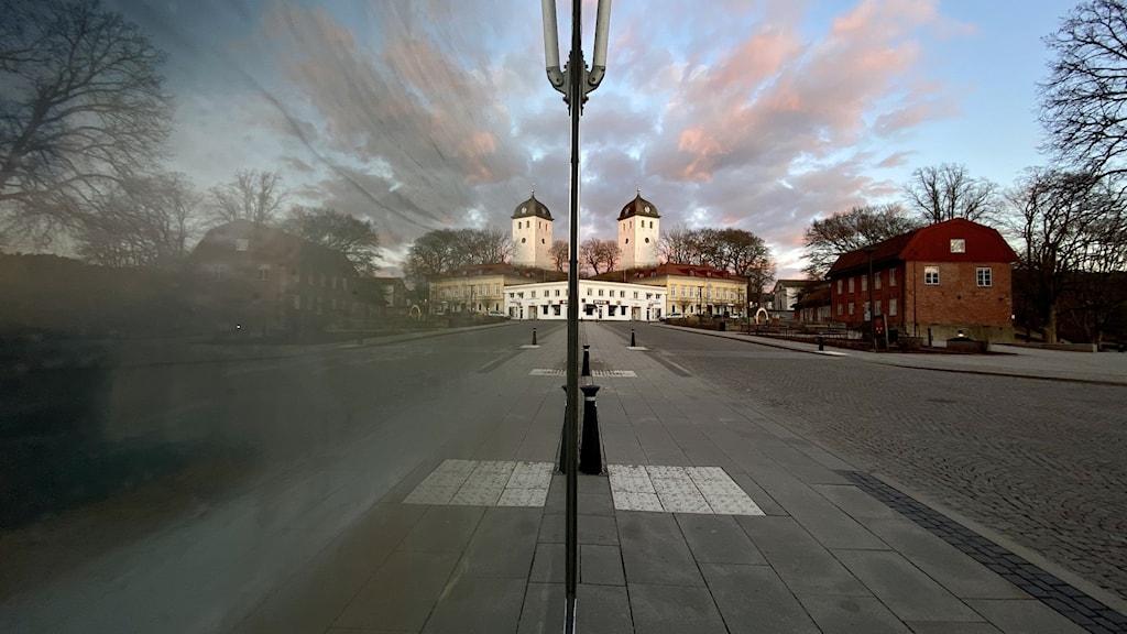 Centrala Uddevalla en eftermiddag i mars. Torget syns på bild, även klocktornet som reser sig över Klockberget. Ett skyltfönster till vänster om bild gör att staden reflekteras; därav två klocktorn i bild!