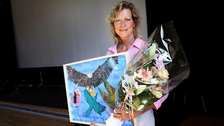Lena Matthijs med blommor och en tavla i famnen