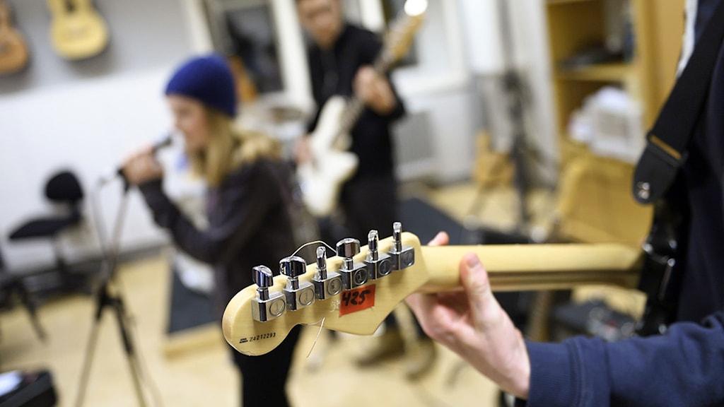 elever spelar på musikinstrument. i förgrunden en gitarr.