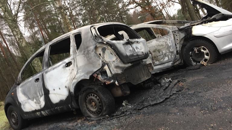 Två vita totalt utbrända bilar.