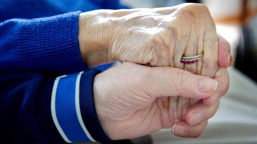 Ett äldre par håller varandra i händerna. Foto: Jessica Gow/TT.