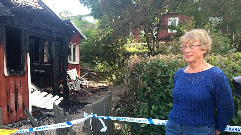 Ann-Britt Johansson framför den nedbrunna hembygdsgården i Lilla Edet