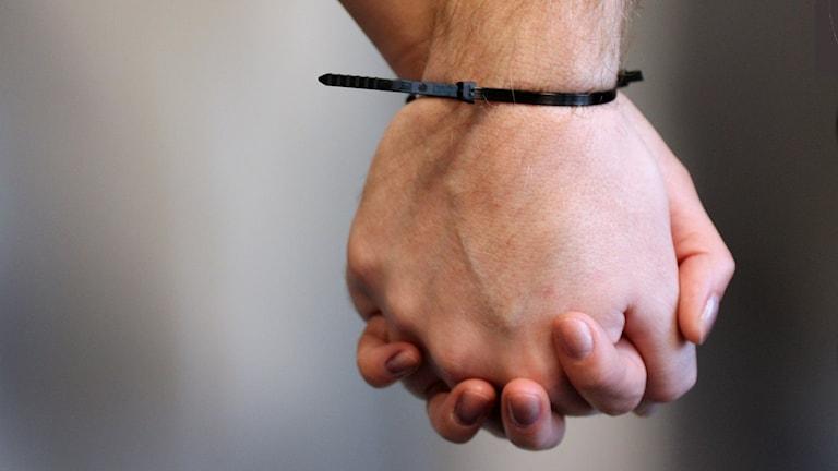 Närbild på ett par som håller handen med en kabelstripe som binder samman deras händer. Foto: Julia Forsberg/Sveriges Radio