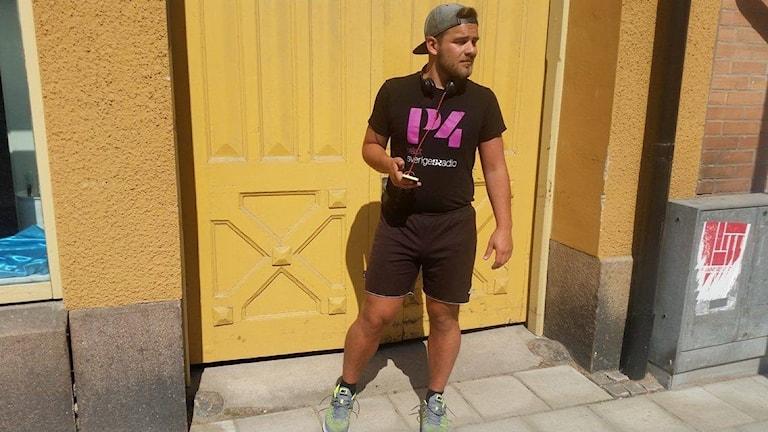 Tommy Öster i shorts och tshirt framför en gul port.