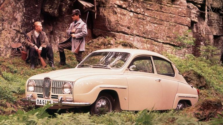 En gammal vit saab bil. En veteranbil. I bakgrunden syns två män. Bilen är fotad i naturen.