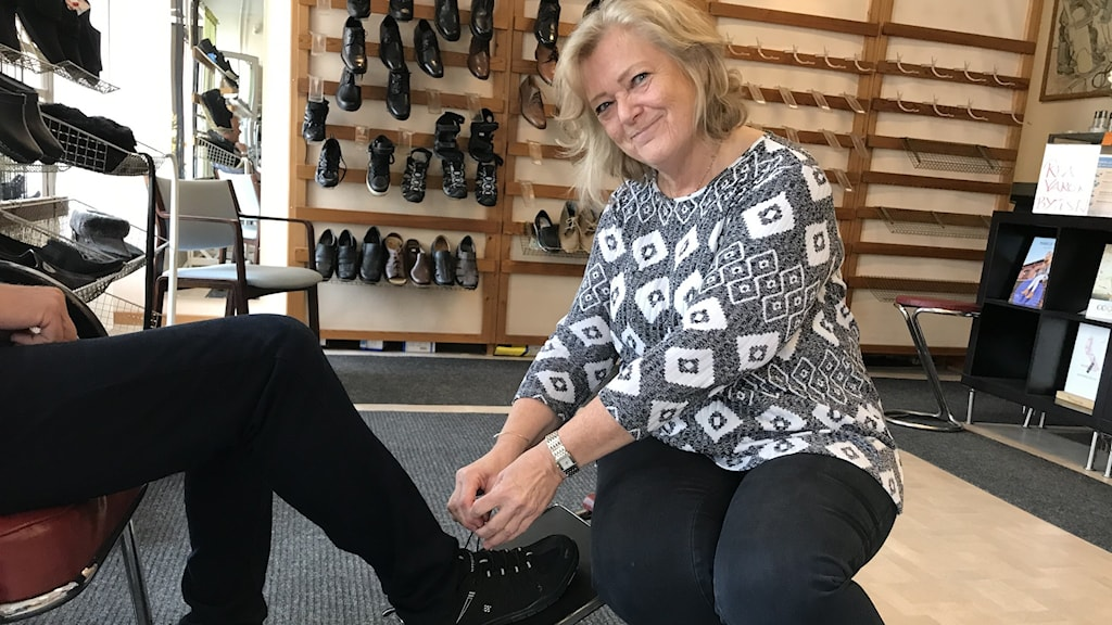En dam hjälper till med provning av sko