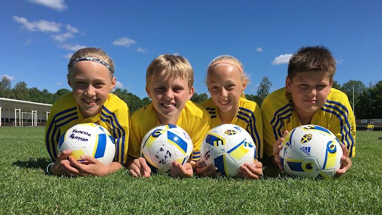 Vanessa Hansson, Erik Heggenes, Saga Fredgren och Simon Strömberg ligger i gräset på fotbollsplanen.