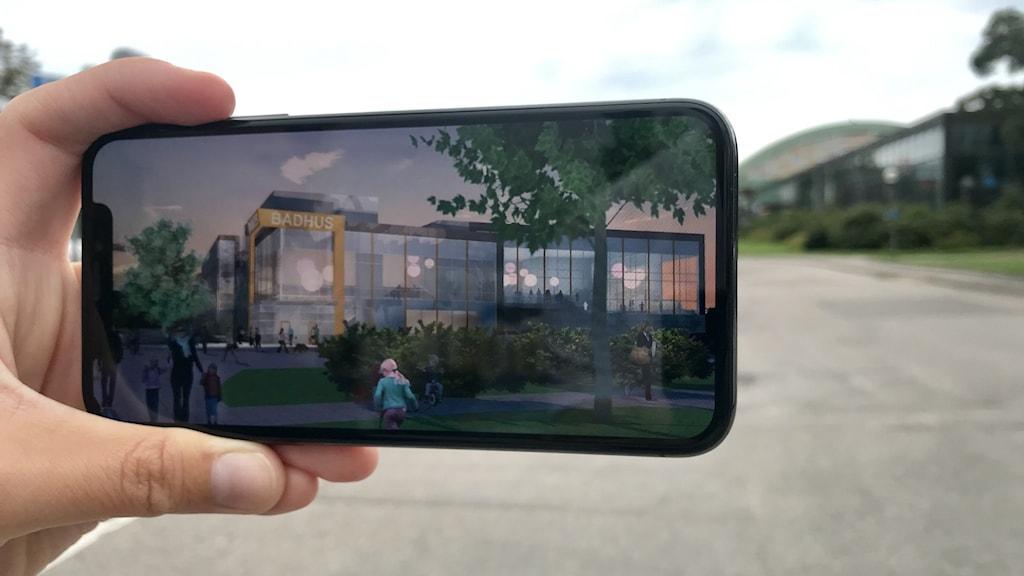 Nya badhuset i Uddevalla. Någon håller upp en mobiltelefon där man ser det moderna badhus som ska byggas, eller inte, på Walkesborg.