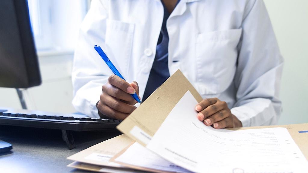 Person i läkarrock letar i papper på ett skrivbord.