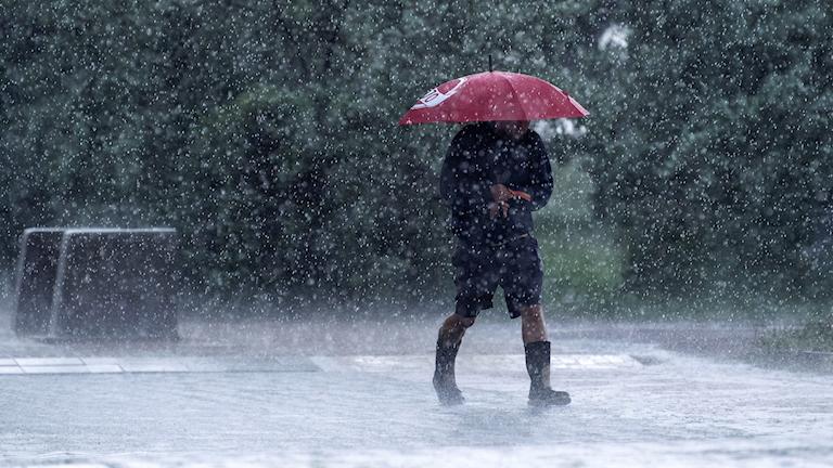 En person går genom ett riktigt ösregn. Han har rött paraply och gummistövlar på sig.